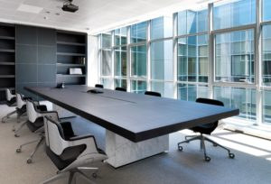 An office conference room with big windows, a table and chairs