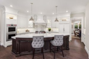 A large kitchen with an island, stools and white cabinets