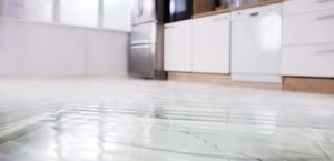 A flooded kitchen floor with cabinets and appliances in the background
