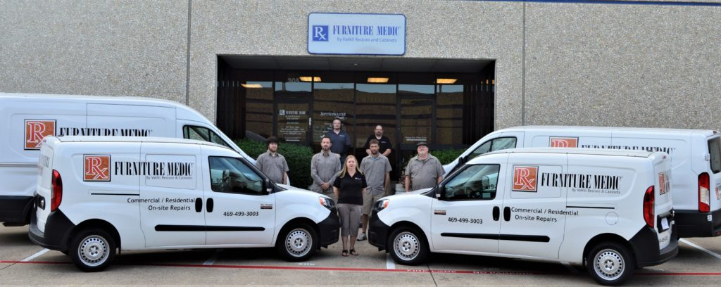 The front of Furniture Medic by VaHill Restore and Cabinets with branded vehicles and employees standing next to them